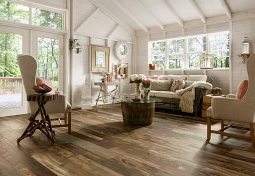 A beautiful living room, in a country-style home, with medium-toned laminate flooring